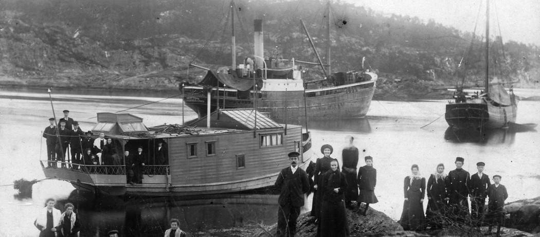"""Fotografbåten """"Ramsøy"""", som reiste rundt og fotograferte.  Mange var møtt opp for å fotografera seg.  Fraktebåten til kaptein Johannes Kviteberg, M/S """"Neptun"""", ligg for anker på Knappen, her var god hamn.  Her ligg og ei Nordlandsjekt, år ca 1910."""